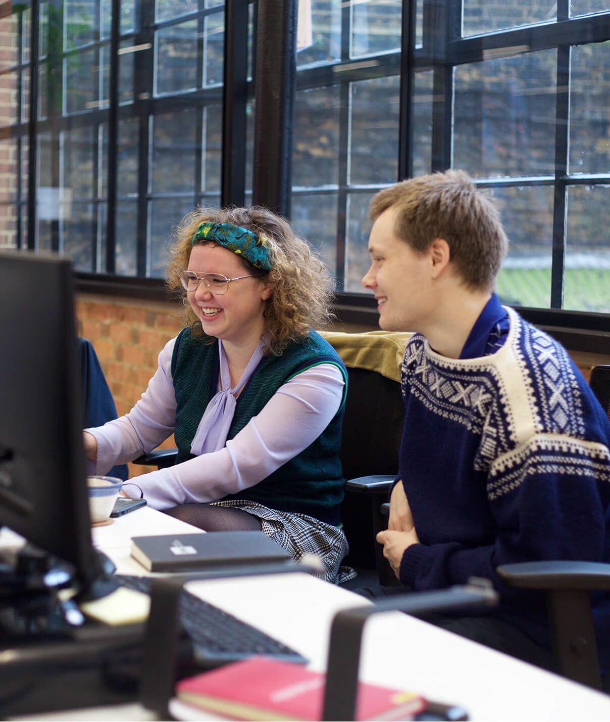 woman and man looking at computer screen smiling