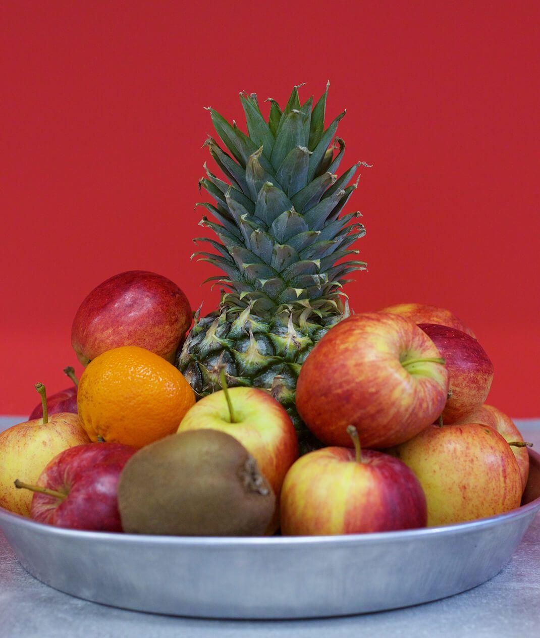 pineapple apples orange kiwi in fruit bowl