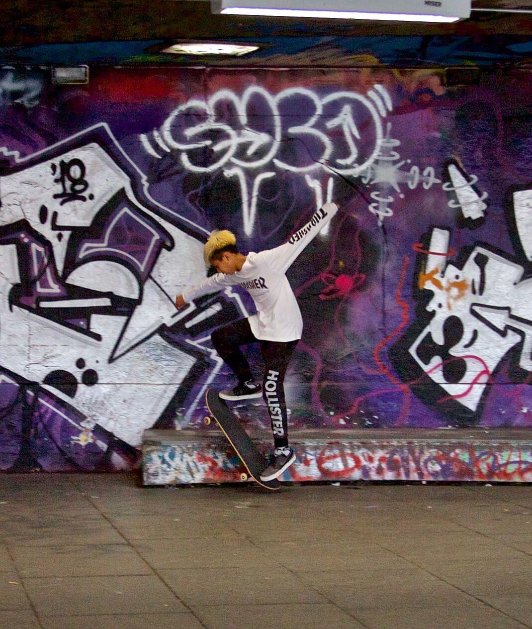 boy with skateboard against purple graffiti wall