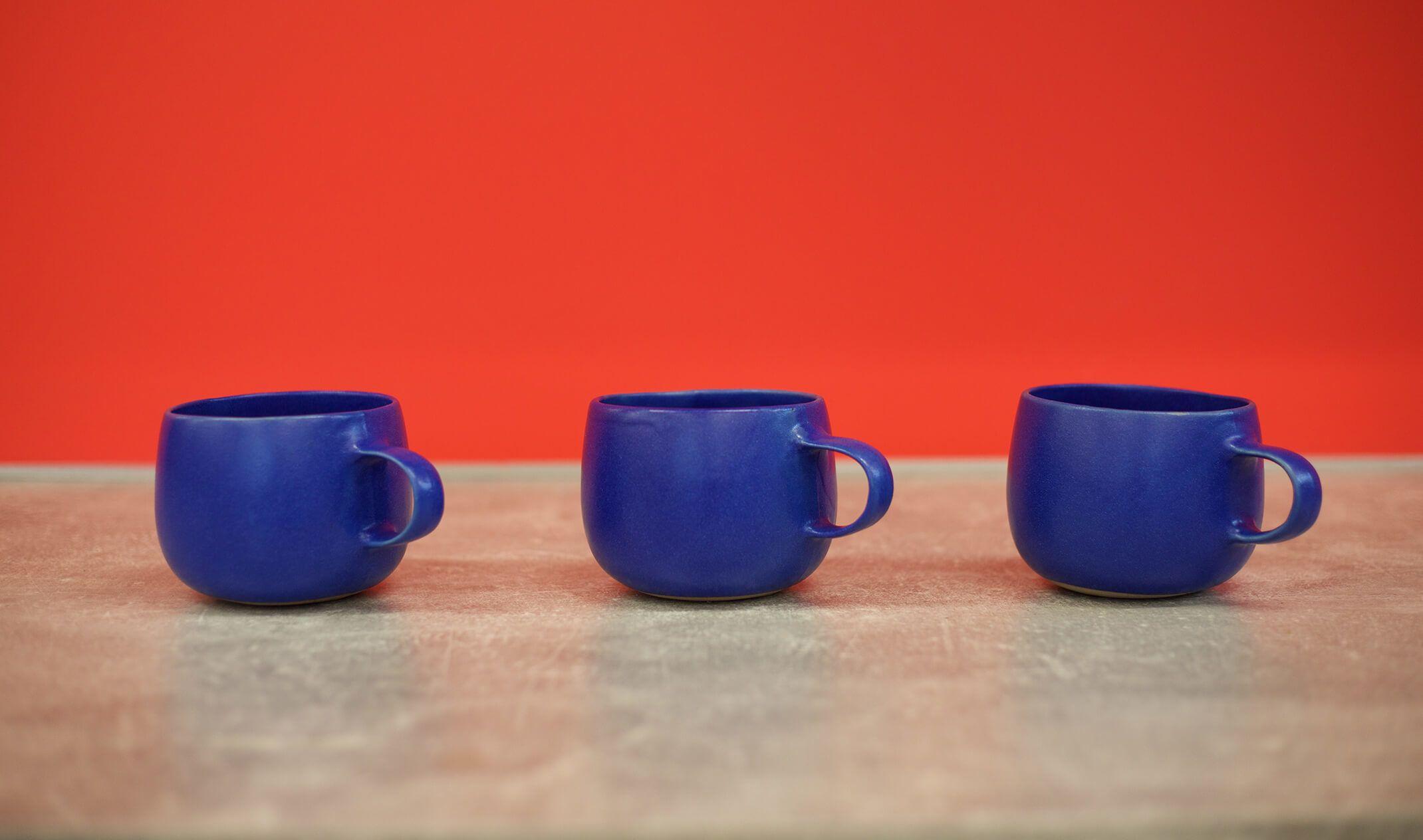 three blue mugs against red wall
