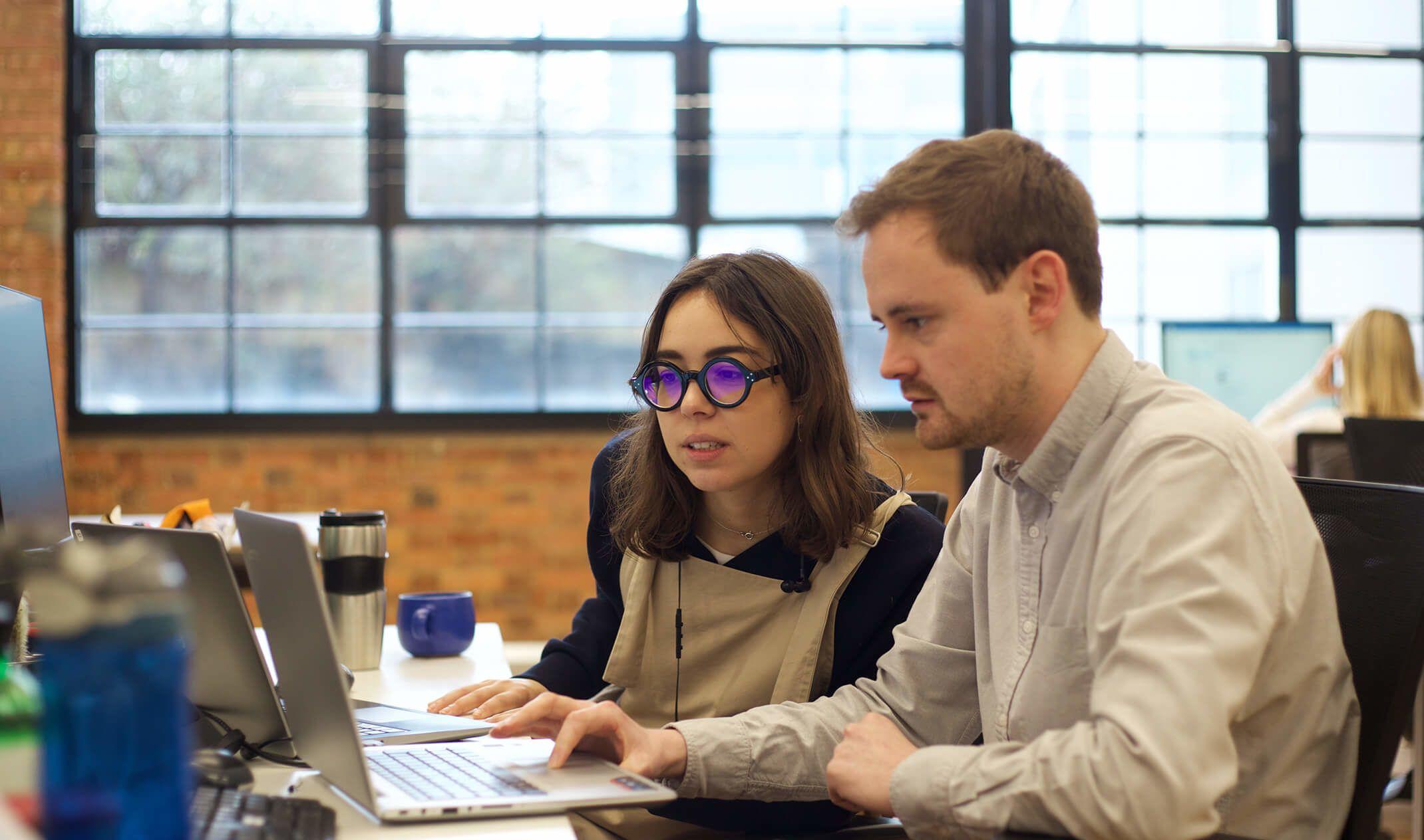 woman and man looking at laptop screen