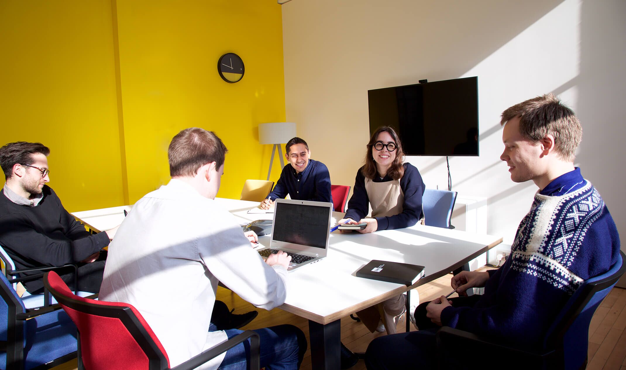 five colleagues sitting at a table in a sunny meeting room