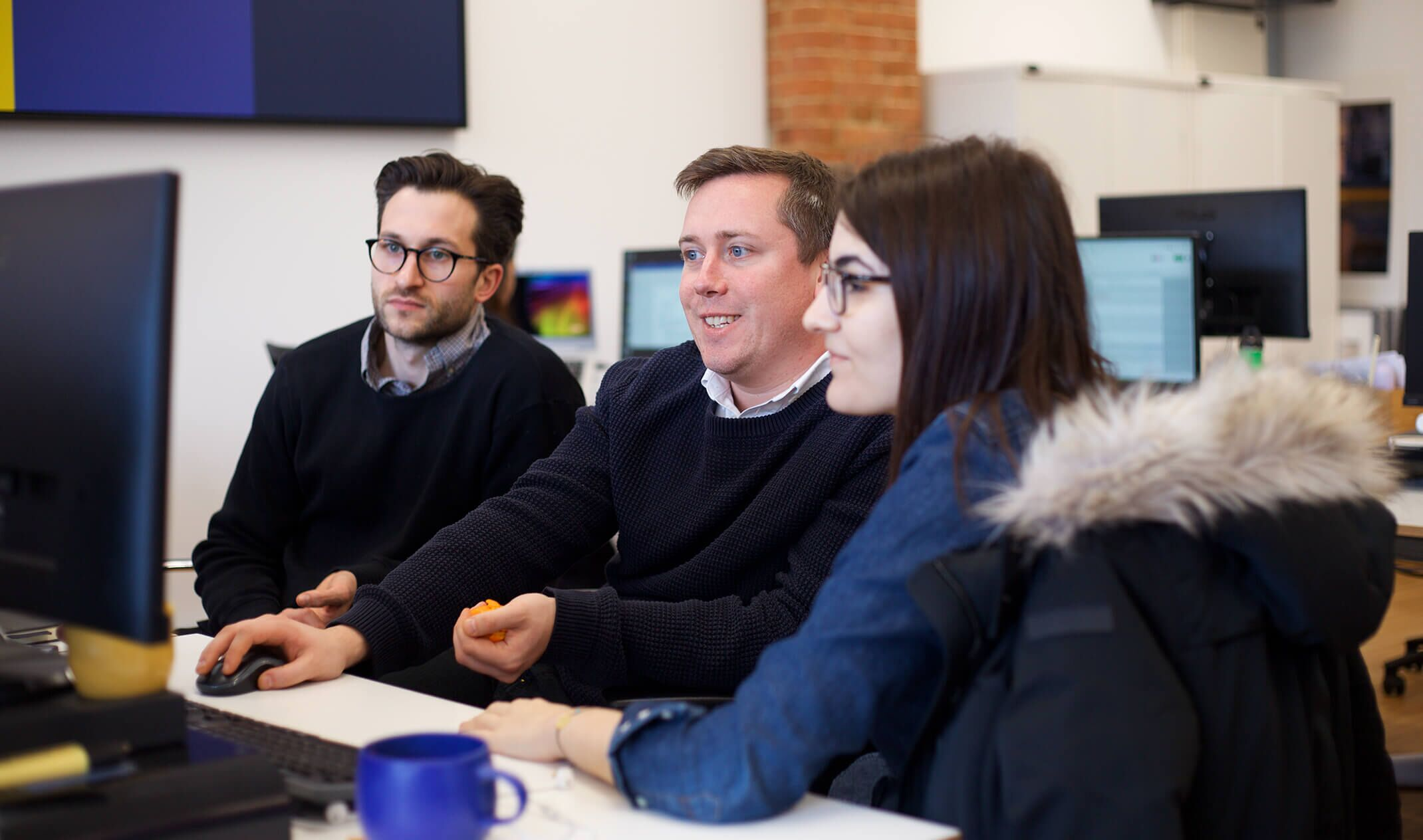 three colleagues discuss work on computer screen