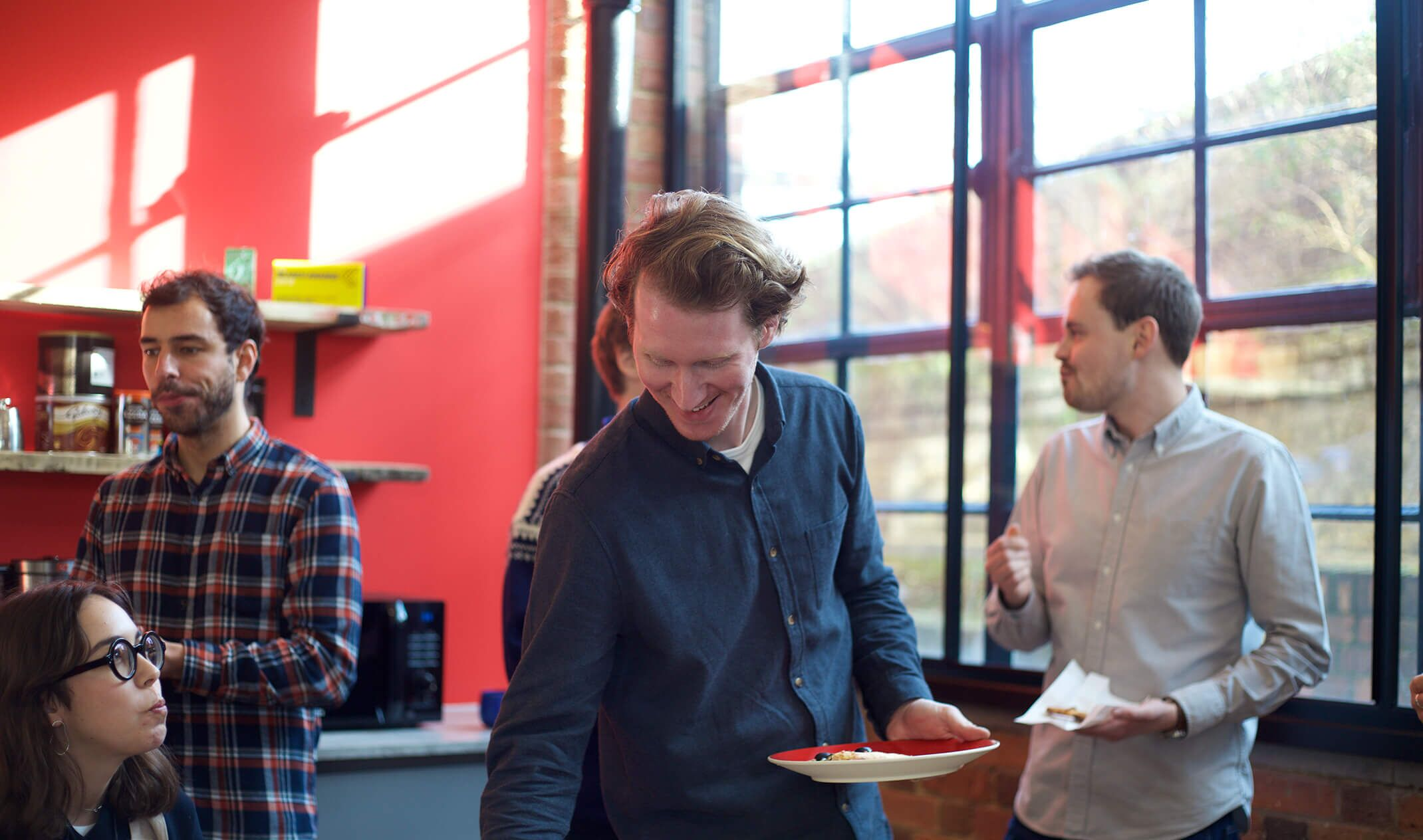 man smiling at work pizza lunch