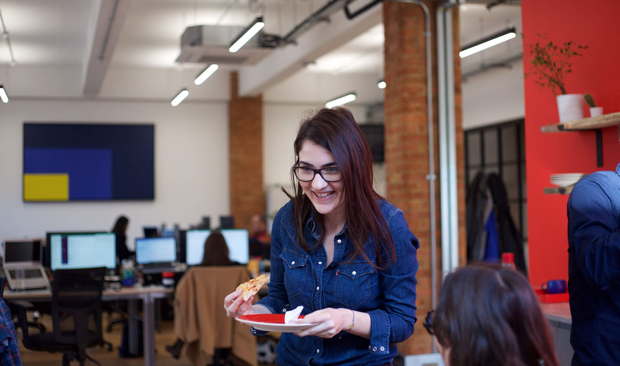 woman smiling holding plate of pizza