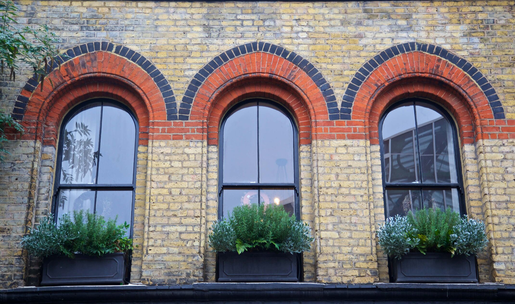 three arched windows of redbrick house