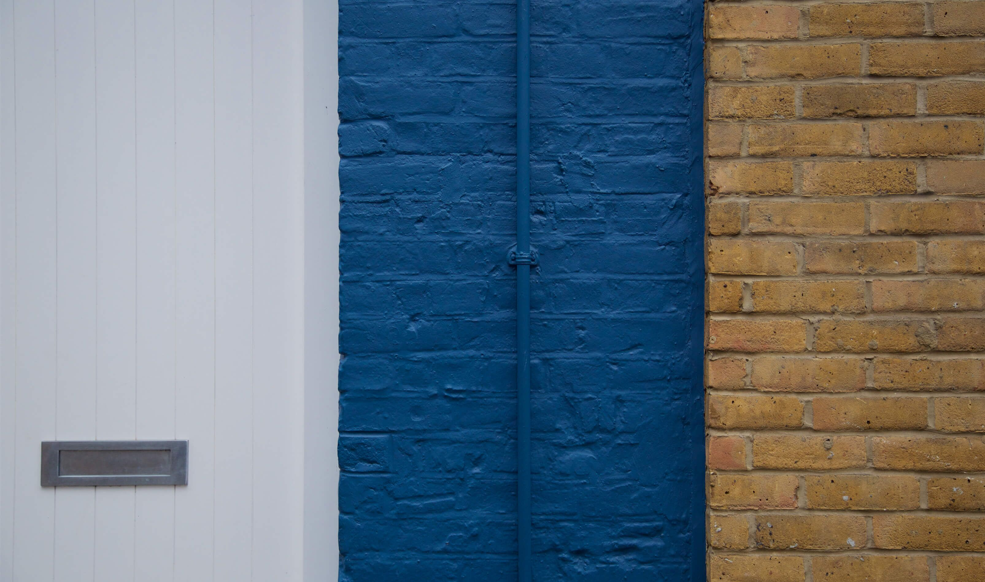 white door brick wall and painted blue wall