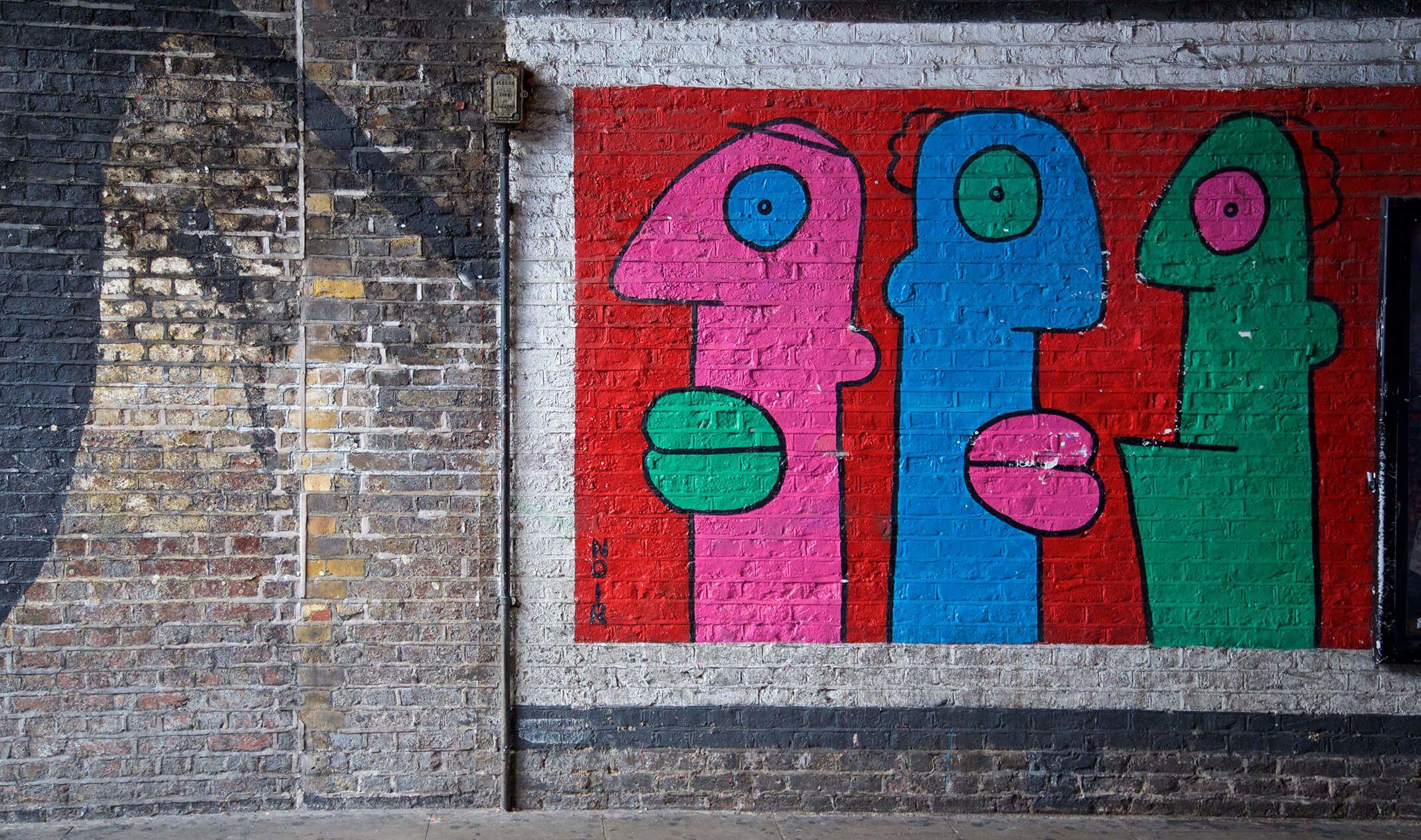 graffiti wall of three heads