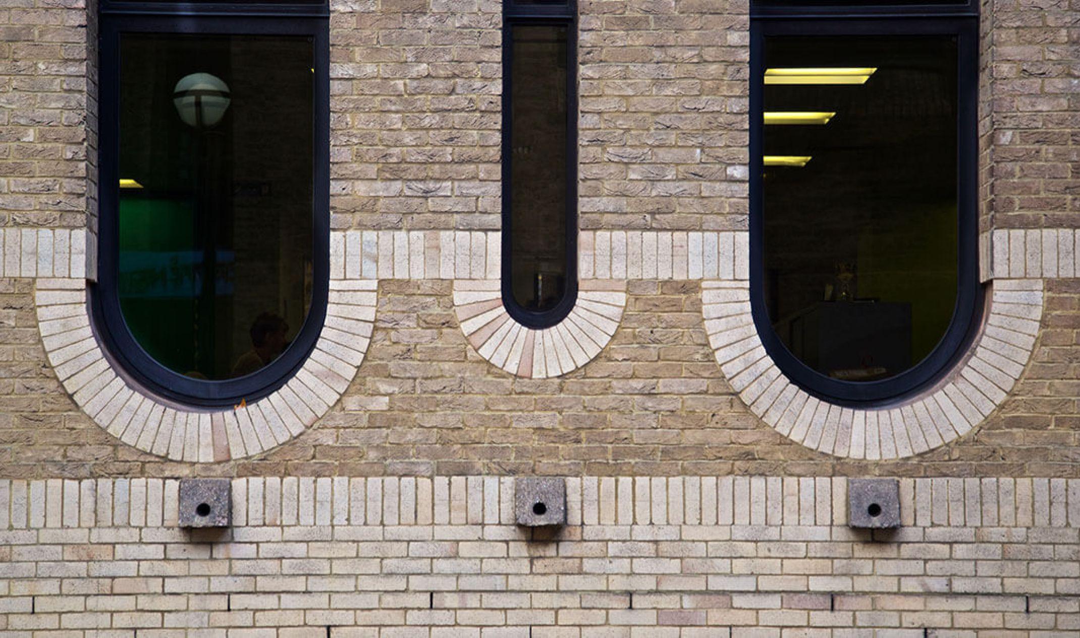brick wall with three circular windows
