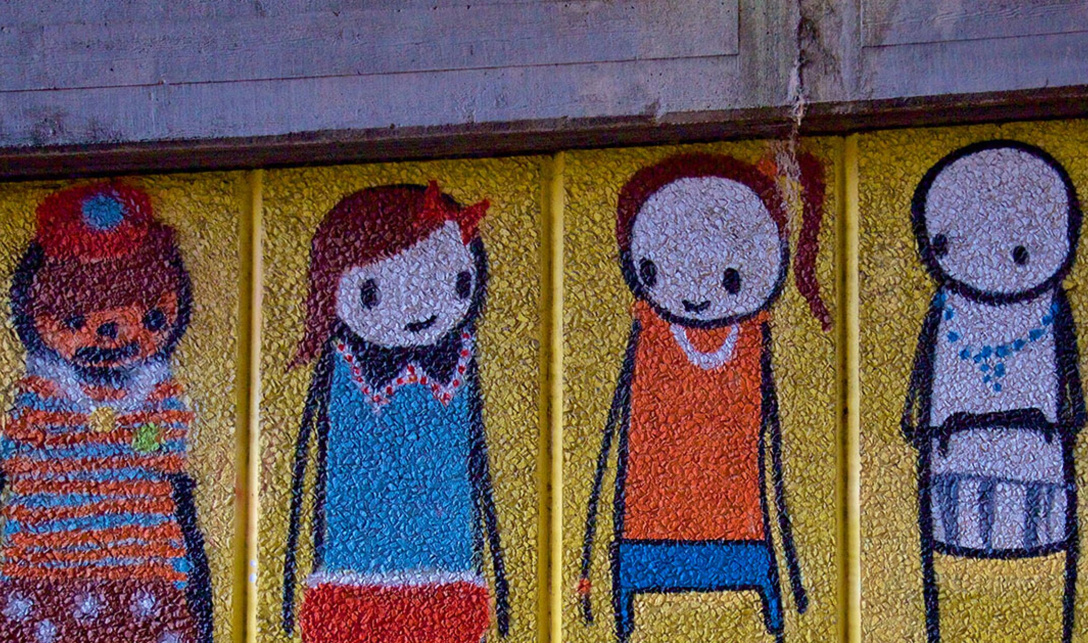 wall of graffiti with five stick figures