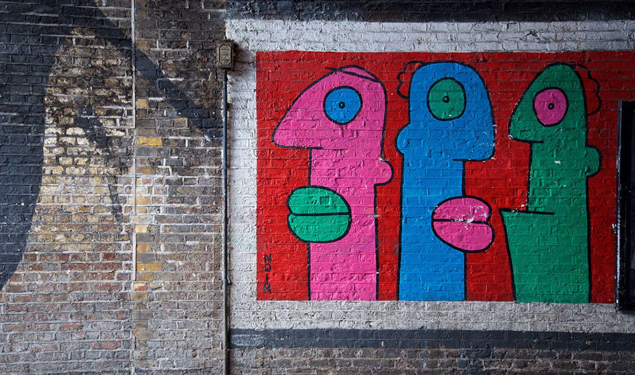 wall of graffiti with three heads
