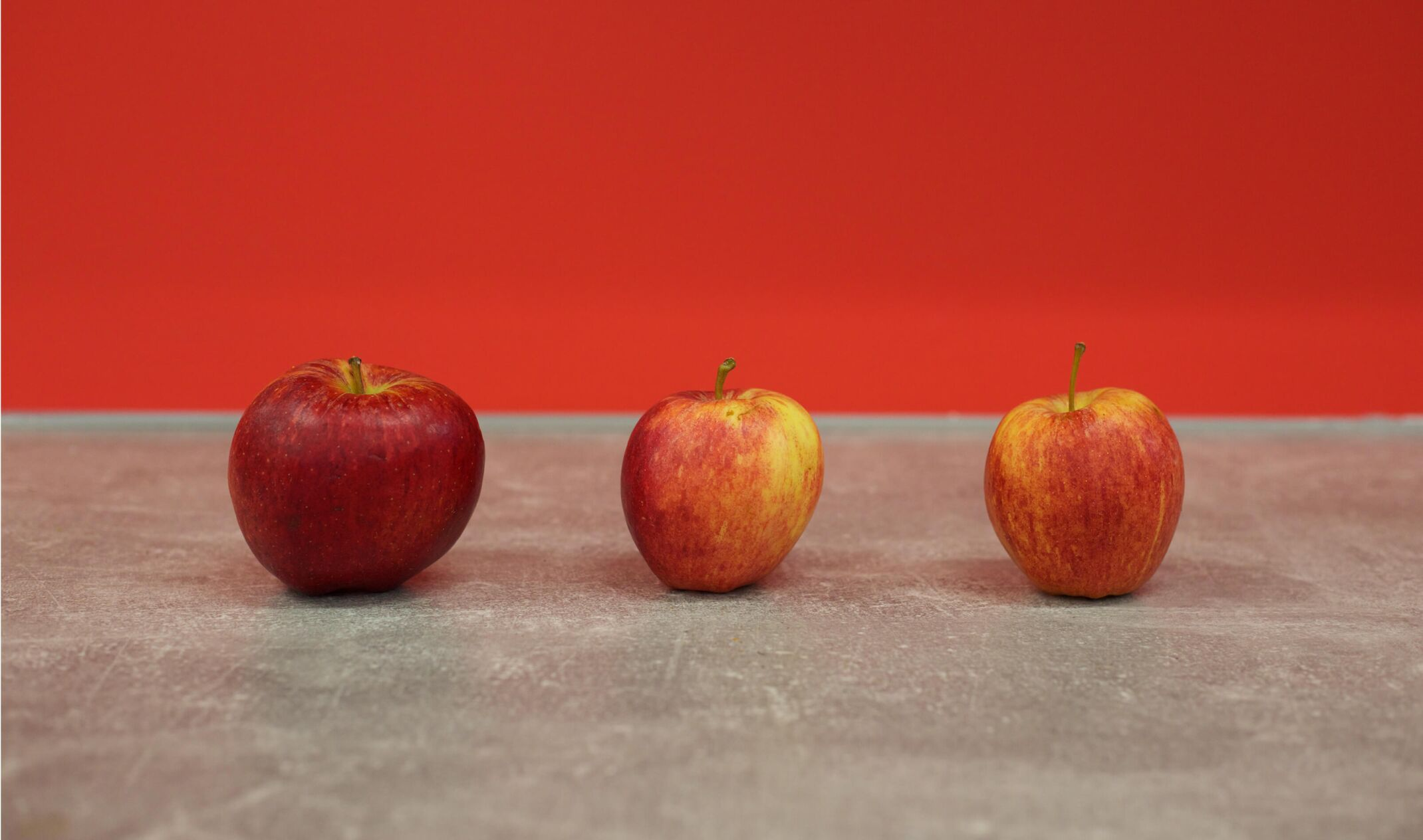three apples on table against red wall