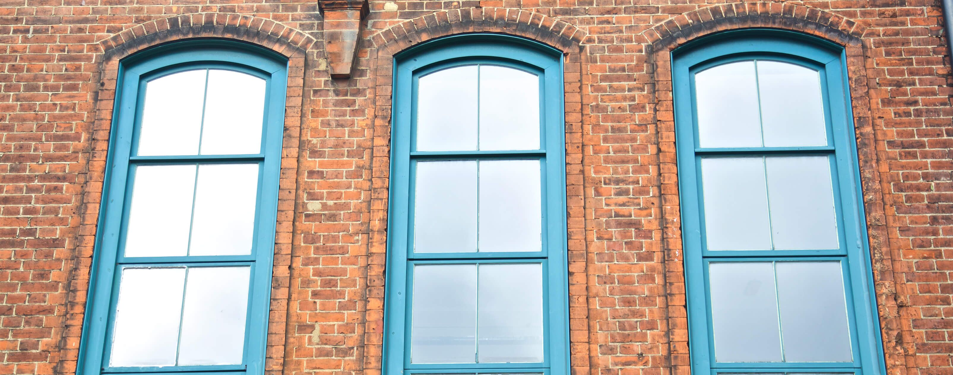three windows with blue window frames of redbrick house